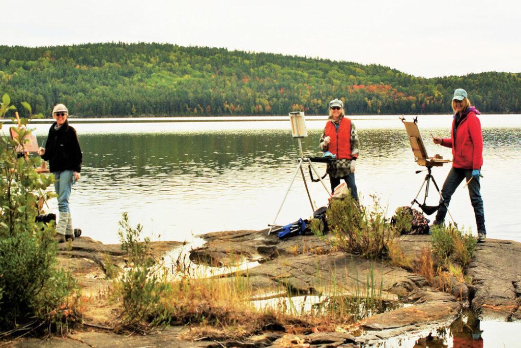 three women painting beside a lake