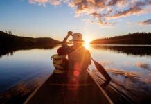 woman and child paddling into sunset stress free