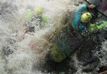 two kayakers crashing in whitewater