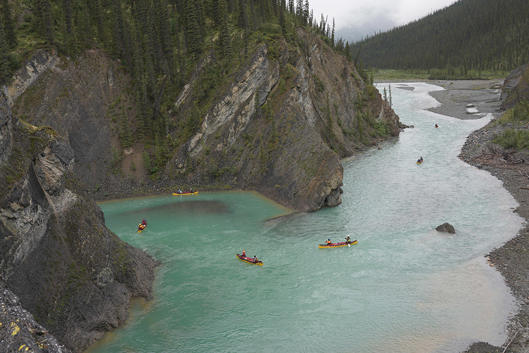 several canoes doing a tandem trip down a river