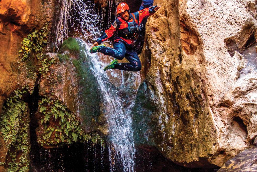 man jumping off a waterfall