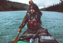 man paddling a canoe in the rain