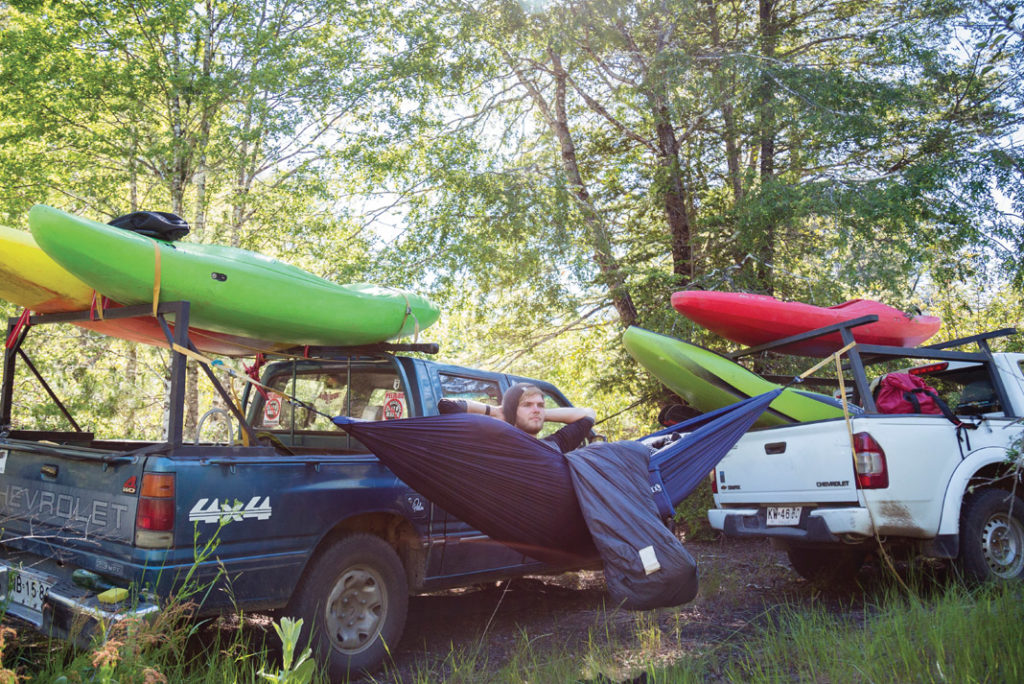 man hanging out in a hammock between two trucks with kayaks on top
