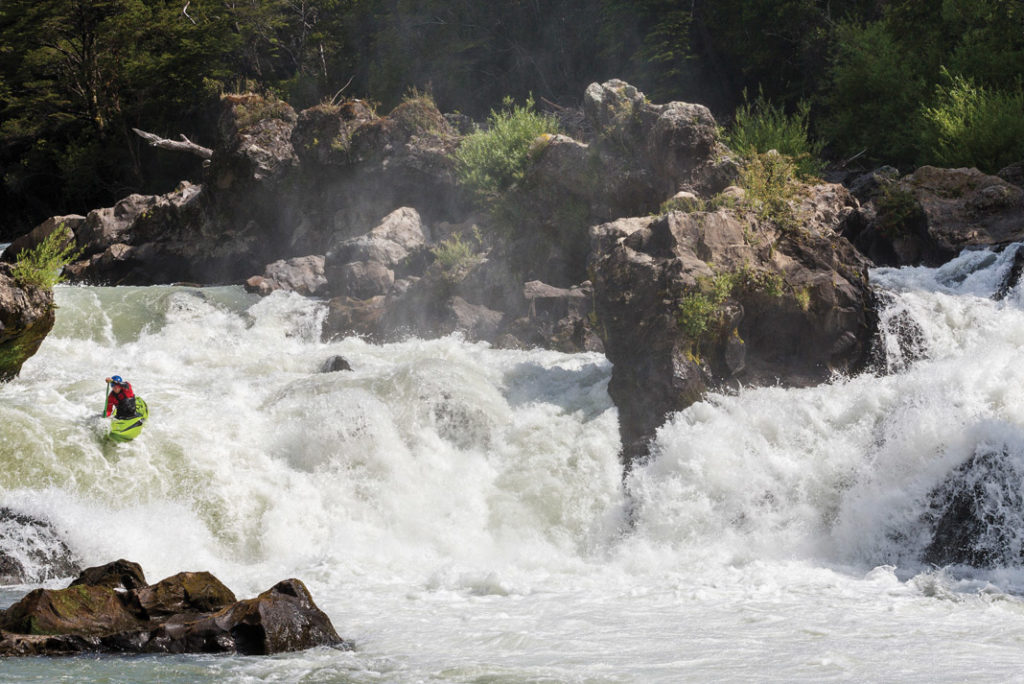 a man in a kayak dropping off a small waterfall