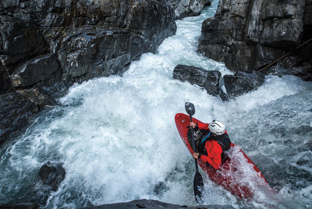 kayaker in a red boat going off a small whitewater drop