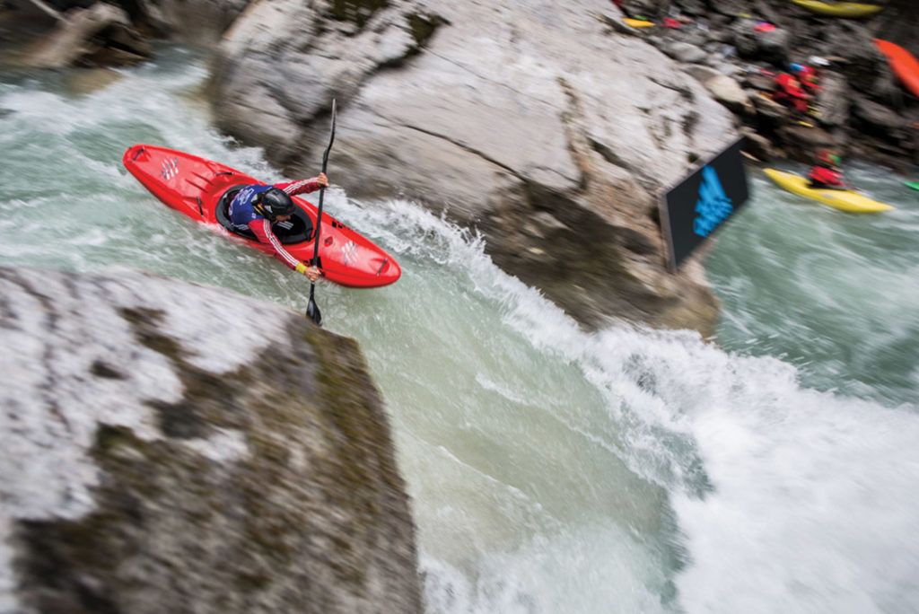 boater in a red kayak racing in whitewater