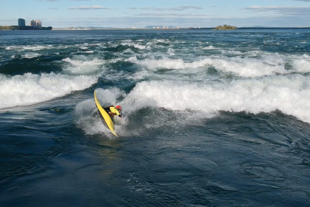 boater in a yellow kayak doing a trick on whitewater waves