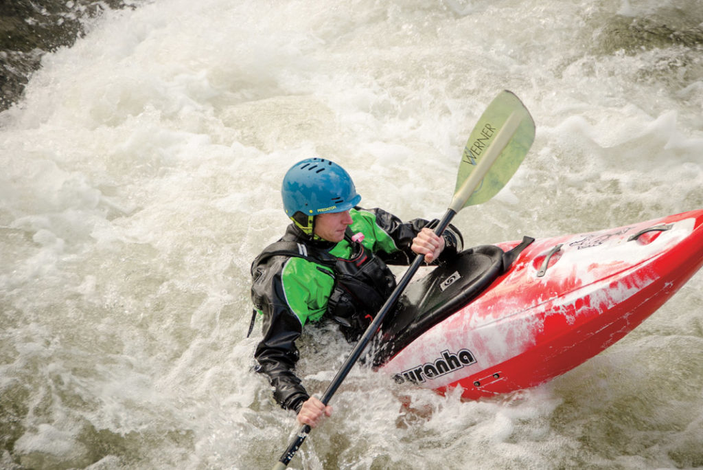 boater in a red and white kayak paddling through whitewater