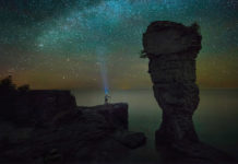 person gazing up at a sea of stars with a headlamp