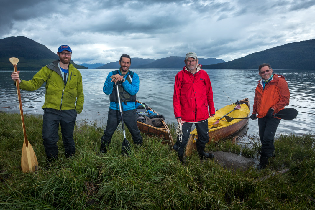 4 people standing in front of a lake with canoes