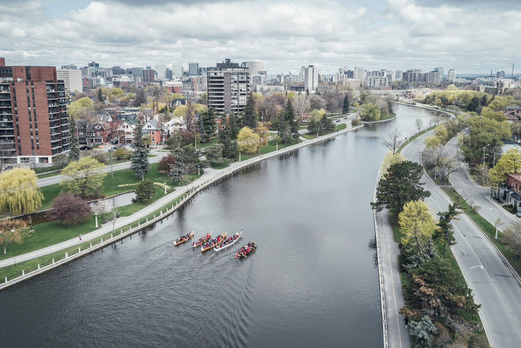 several large canoes paddling through city