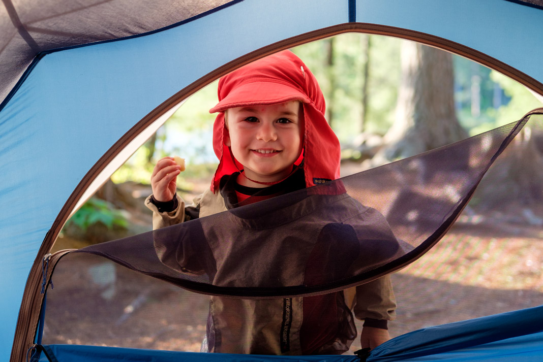 a young boy standing outside of a tent