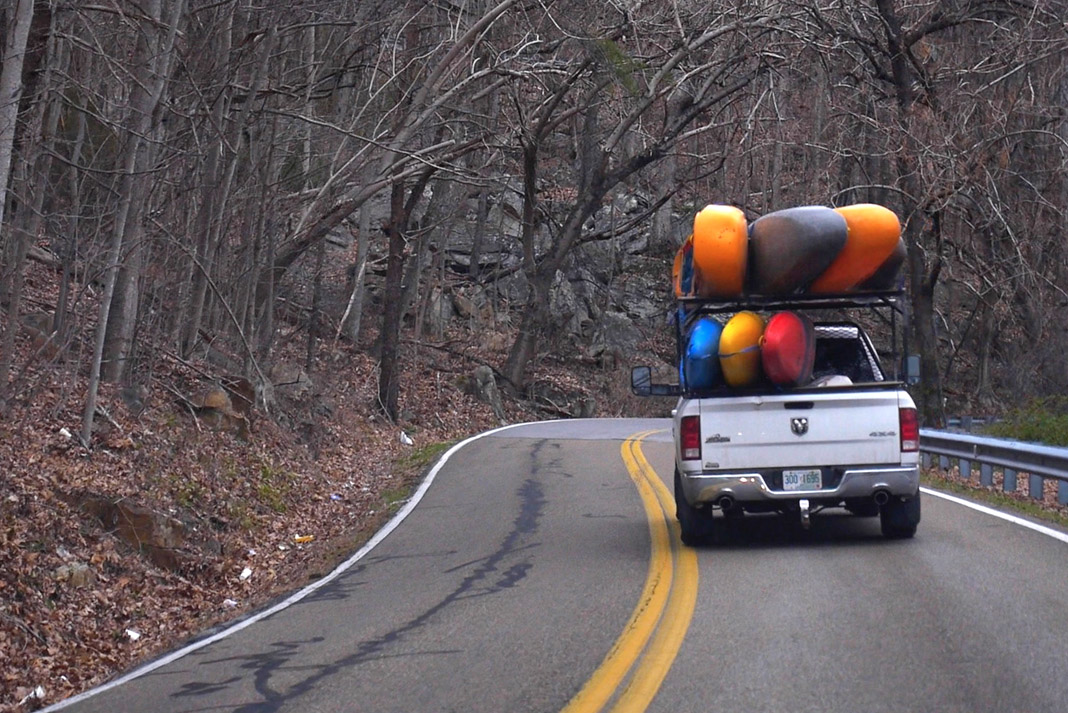 truck with severals canoes strapped on