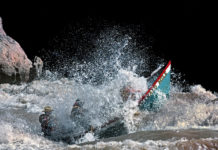 two men in a canoe bursting through a rapid