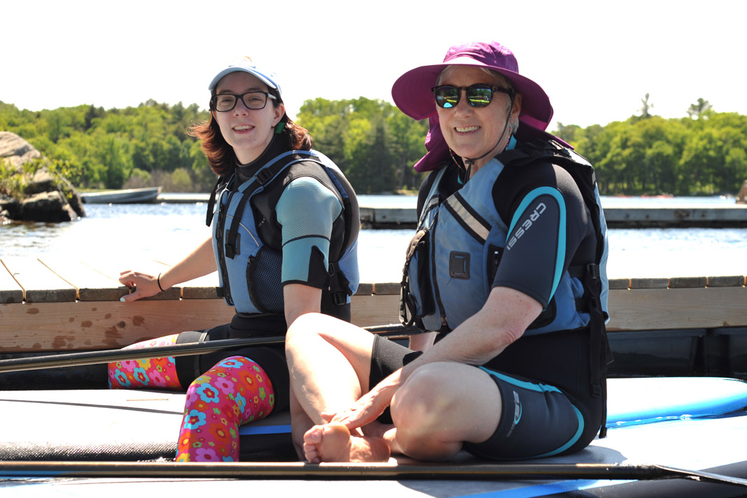 two women wearing paddling gear on boats