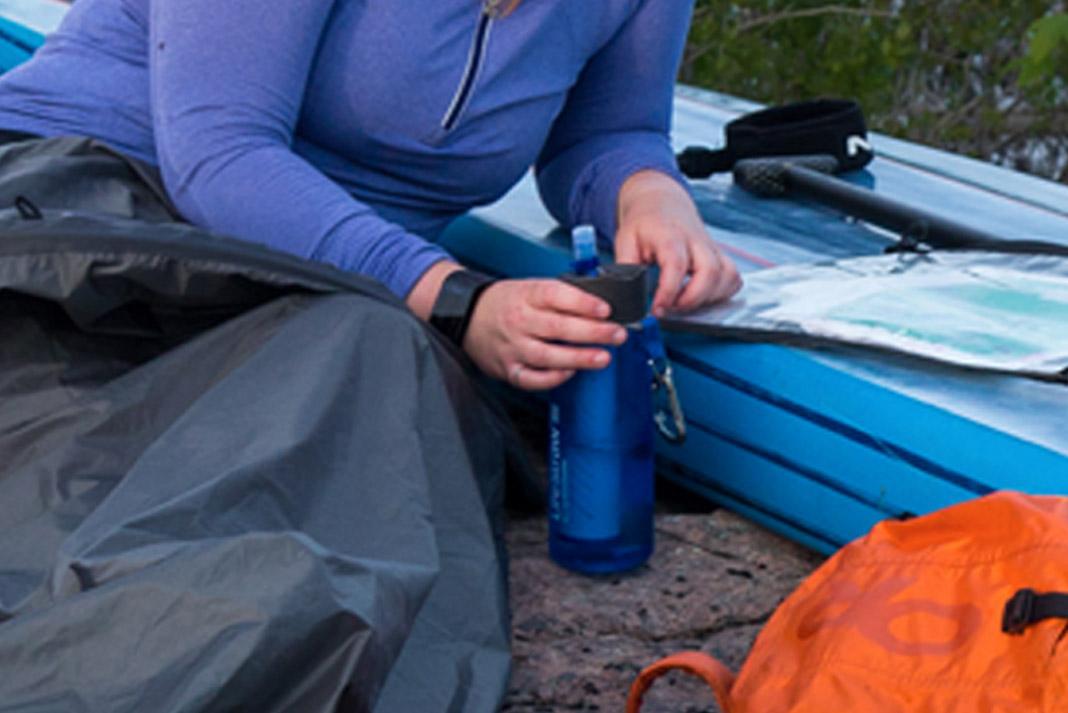 woman wearing watch holding blue water bottle