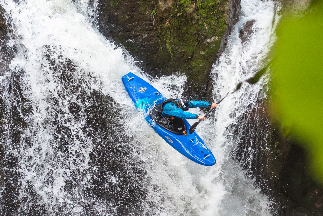 kayaker dropping off waterfall