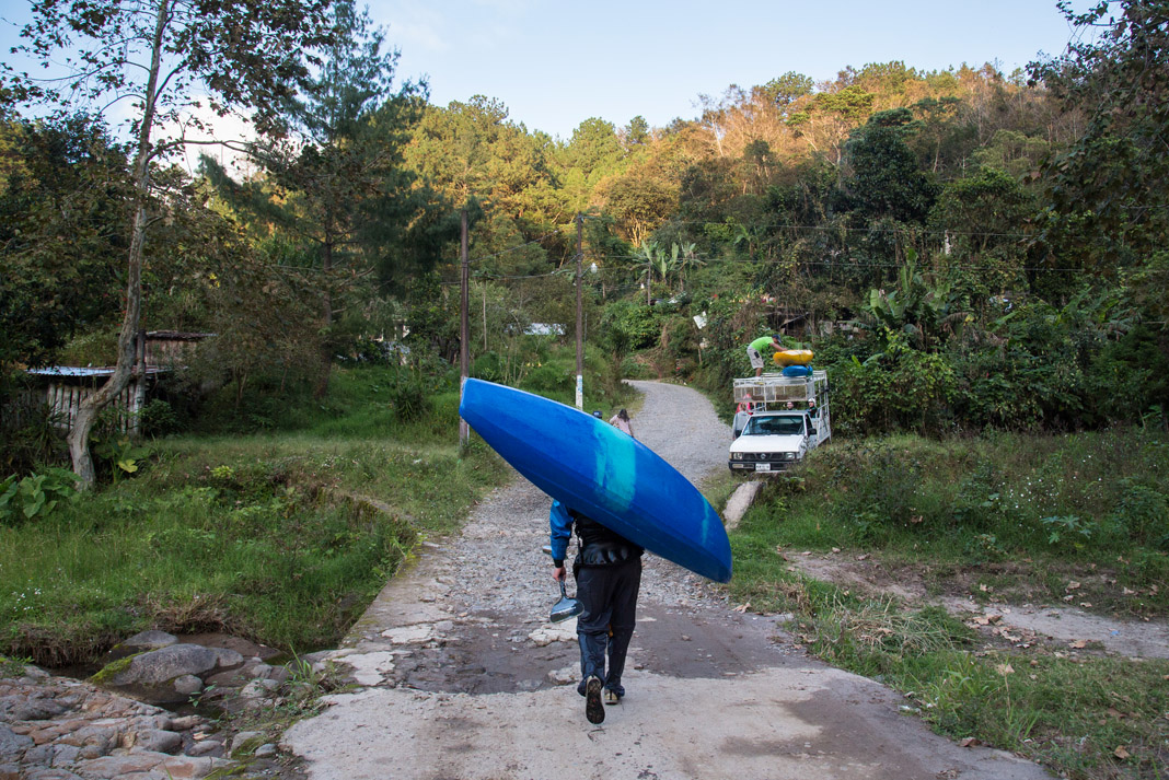 man carrying kayak on his shoulder
