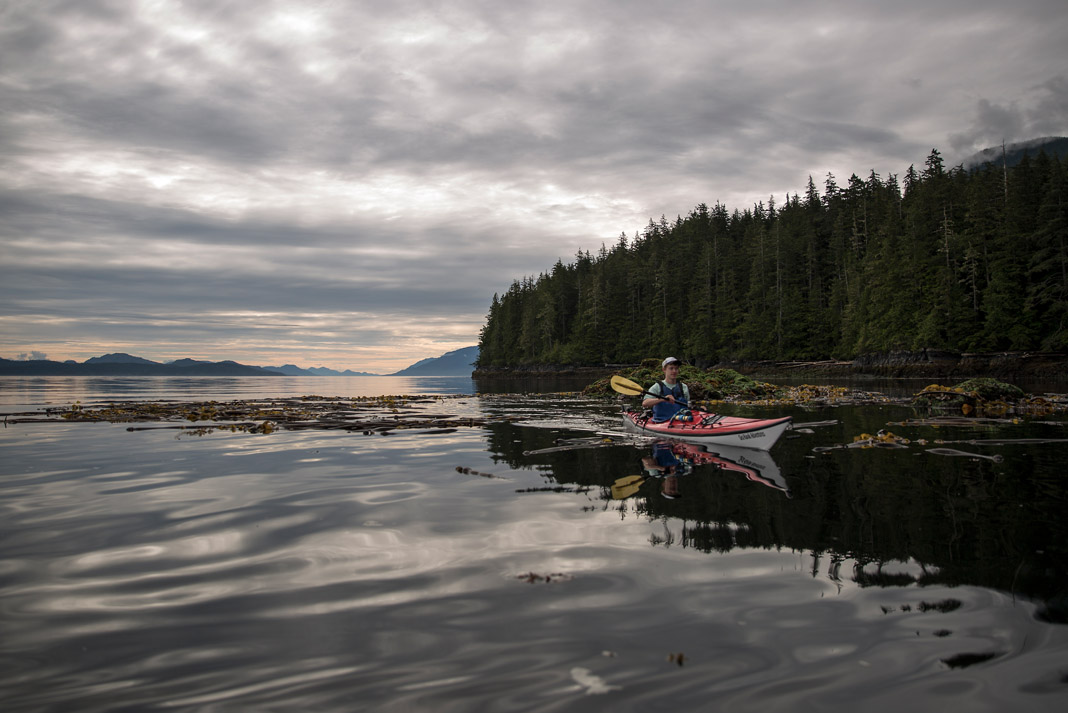 man sea kayaking on lake with scenic background