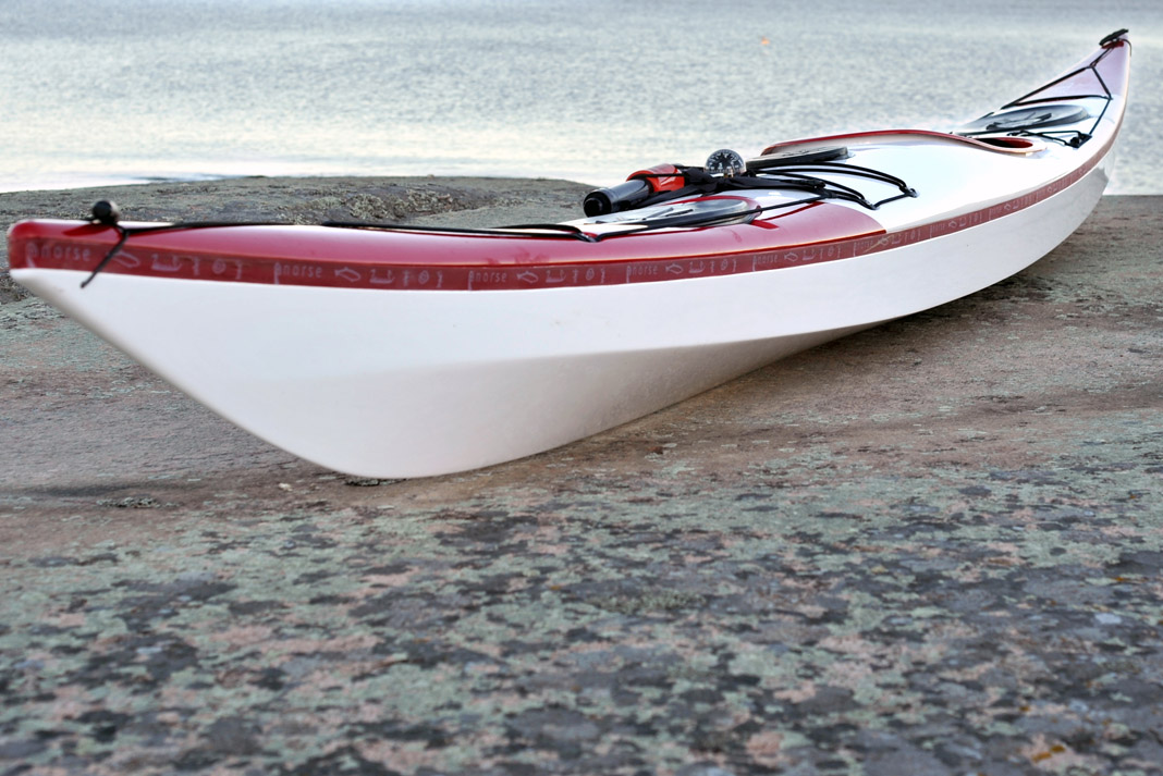 a view of Norse Kayaks' Bylagja sea kayak's upswept bow on shore.