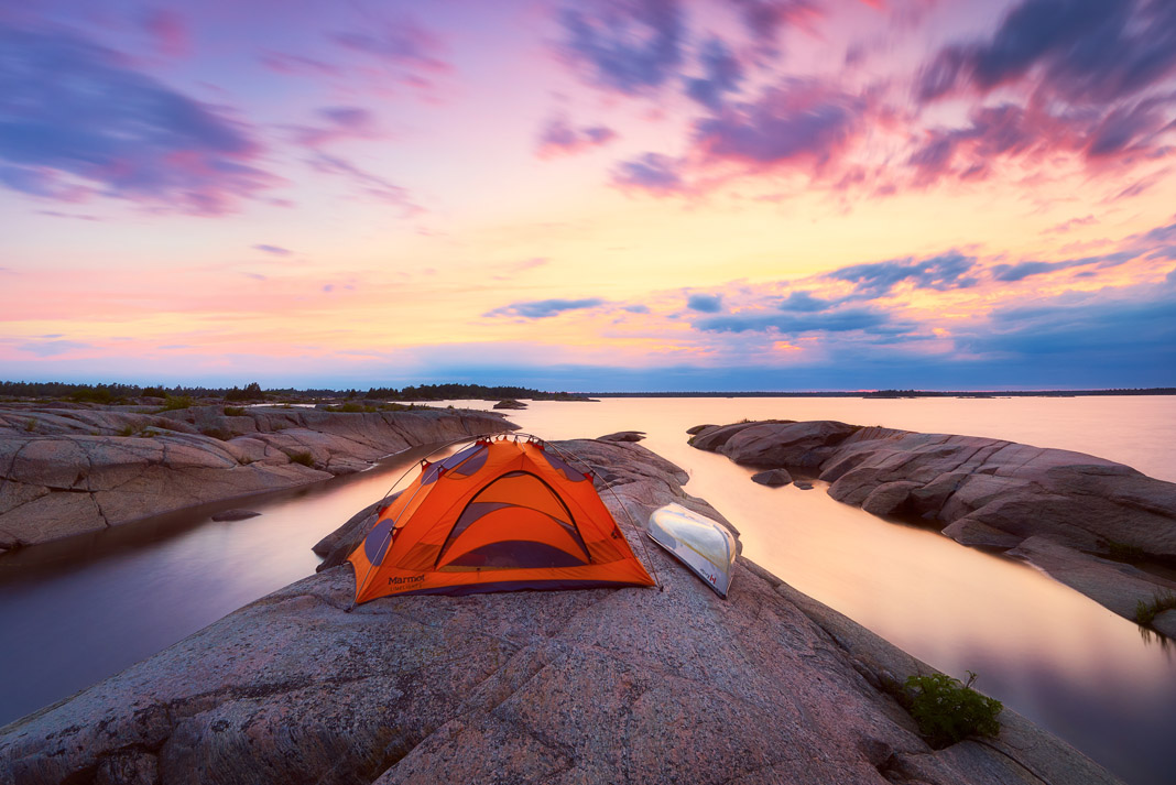 a tent and canoe on an island with a sunset in the background