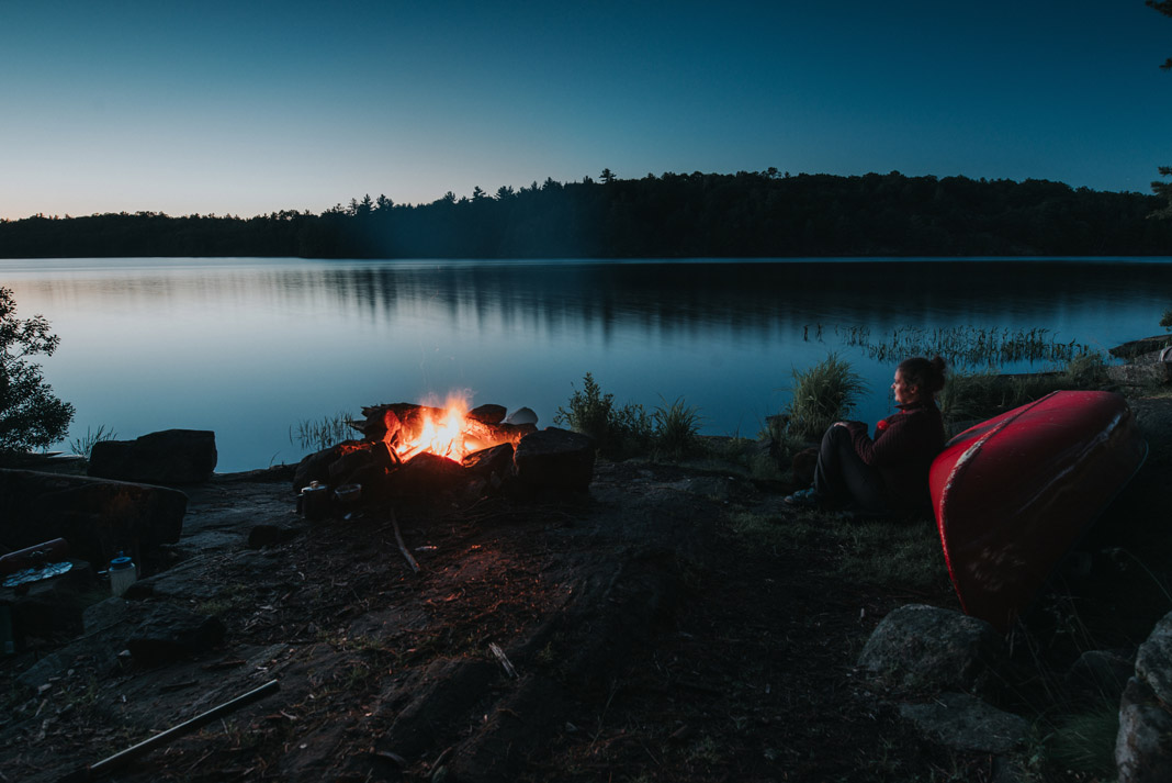 woman sitting against a canoe in front of fire