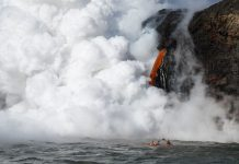 lava pouring out of a volcano into the river causing lots of steam