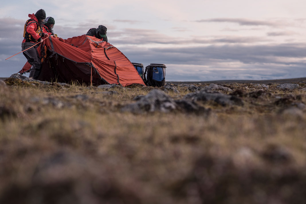 three people setting up a tent in vast territory