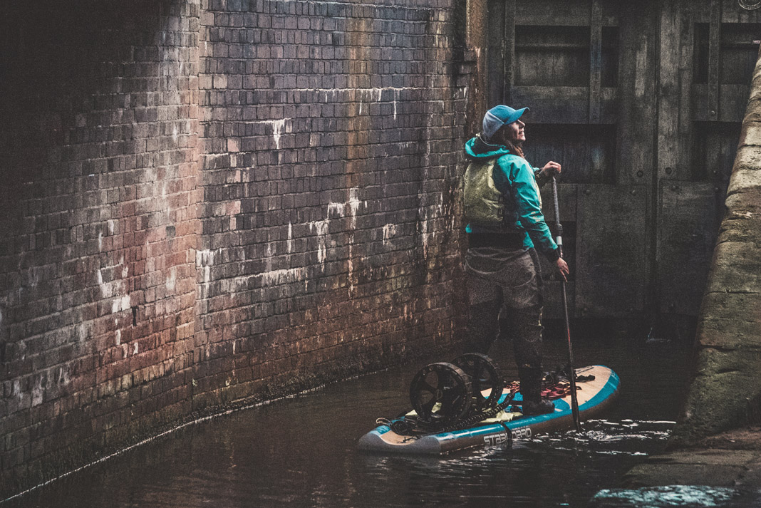 paddleboarder surrounded by city walls