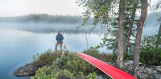 man standing on an island with a canoe