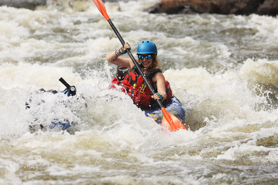 woman paddling through rapid smiling