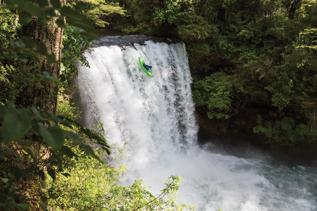 kayaker paddling off a waterfall