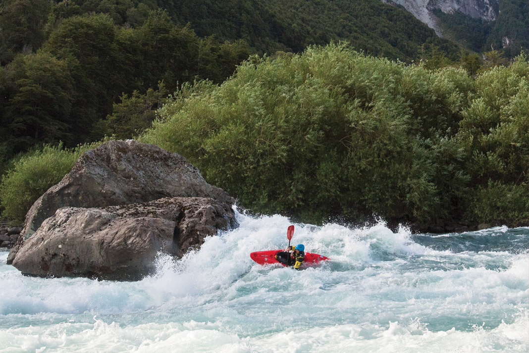 kayaker paddling crystal blue whitewater with scenic view