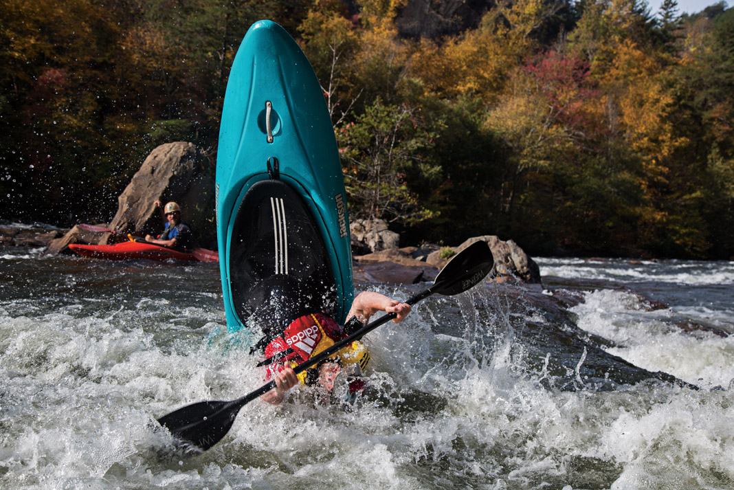 boater flipping his blue kayak in a whitewater rapid