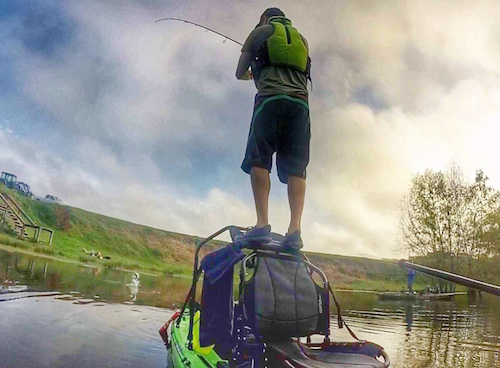 Kayak angler stands on a cooler on top of his kayak and he is fishing.