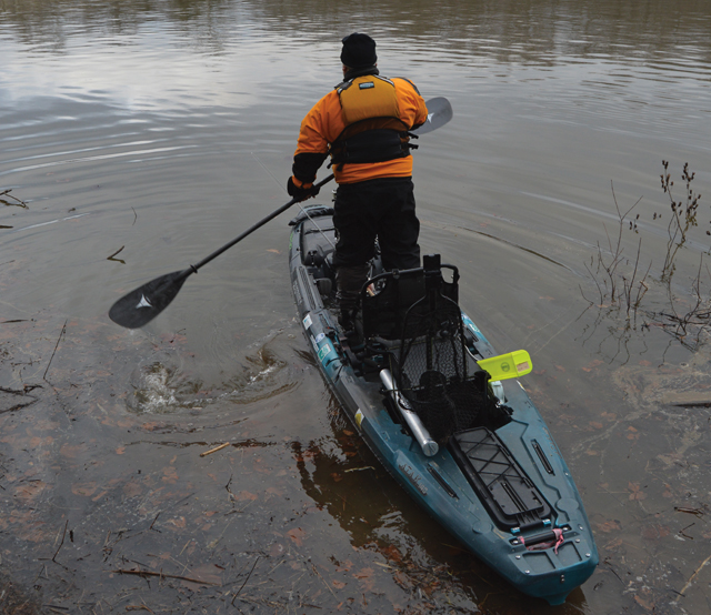 A kayak angler standing and paddling out to fish.