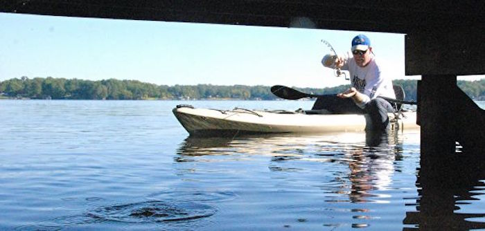 A kayak angler casts under a wooden dock.