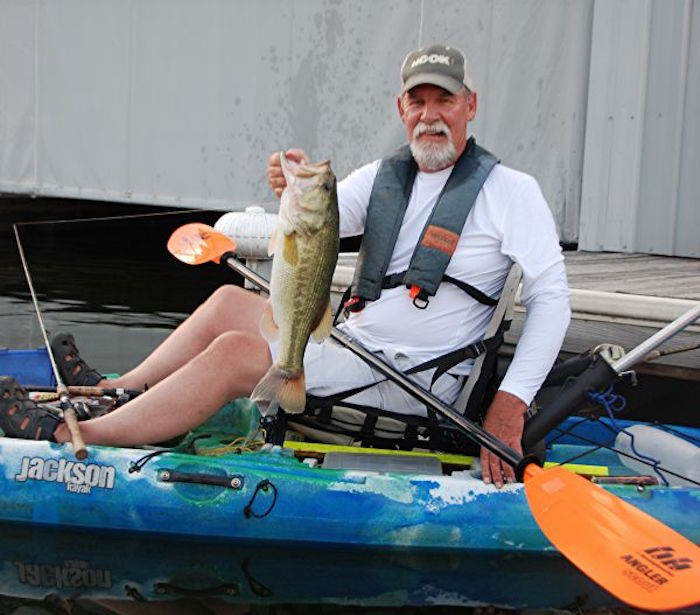 A kayak angler holds up a large fish in front of a large boat house as he sits on his Jackson fishing kayak.