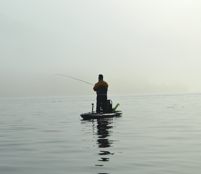 A kayak angler standing and fishing in the fog.