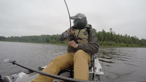 Ben Duchesney sits on his fishing kayak as he reels in a presumably big fish.
