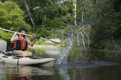 Ben Duchesney sits on his fishing kayak and splashes water at a lure stuck in a branch.