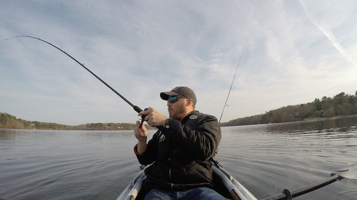 Man reels in a catch while seated in his fishing kayak