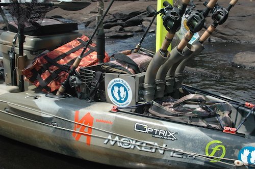 An wide-angle picture of the stern of a Moken 12.5 fishing kayak that is rigged with fishing rod holders.