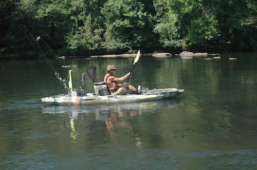 A side view of Eddie McRae paddling his fully-loaded Moken 12.5 fishing kayak.