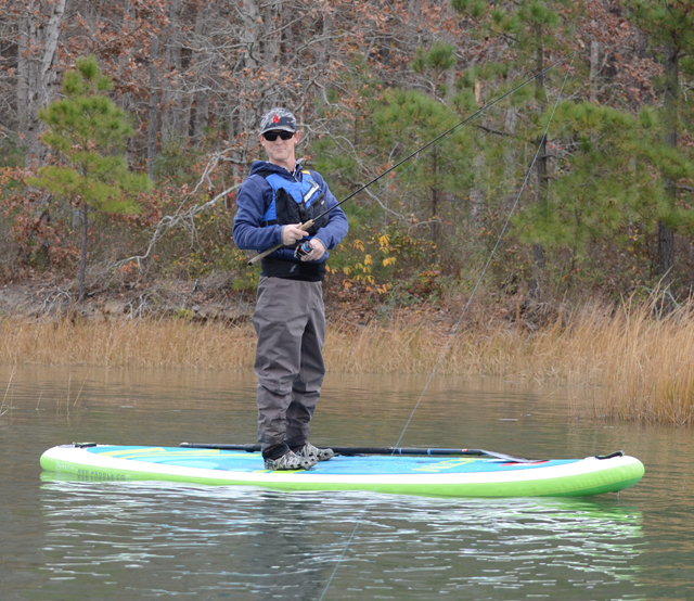 A kayak angler standing on an Red Paddle Co. Activ SUP