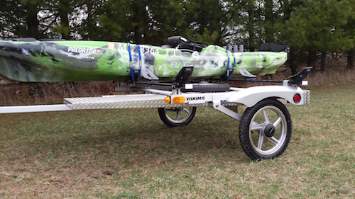 A side view of Craig Hefner's Old Town Predator Fishing Kayak strapped to a kayak trailer