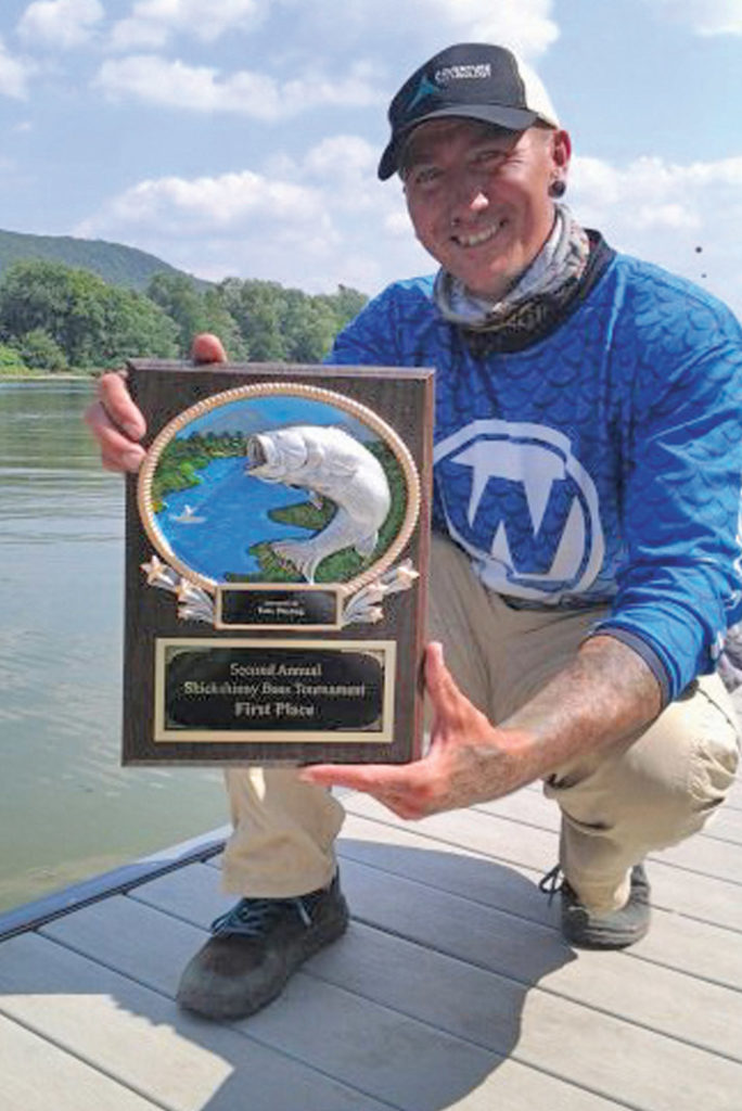 Jedediah Plunkert holding fishing tournament trophy