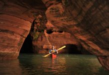 Kayaker paddles through red caves
