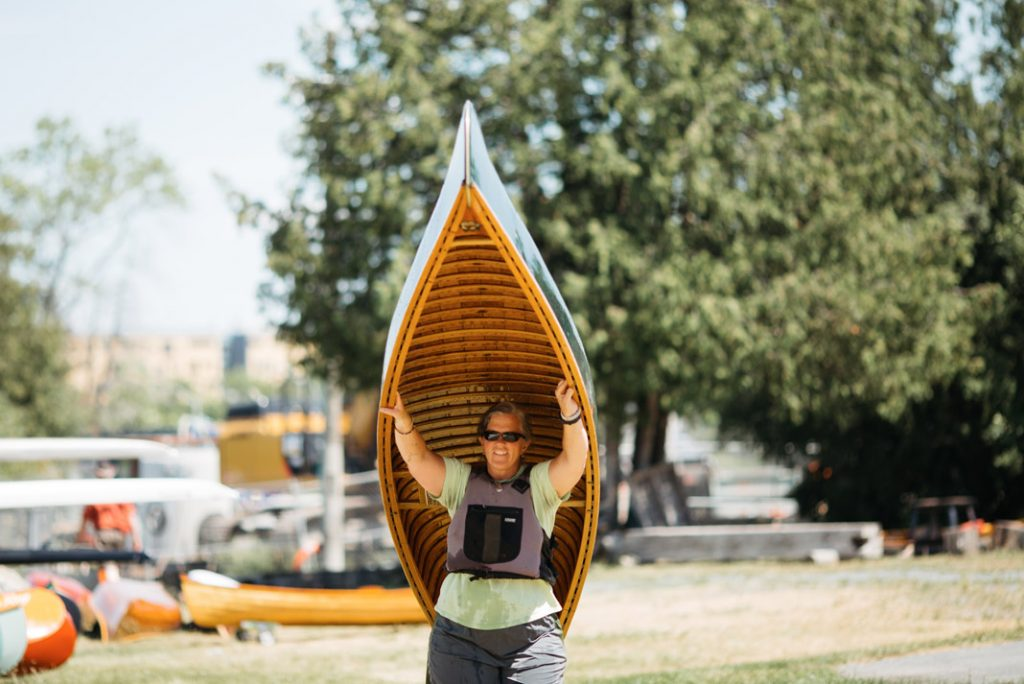 Woman holding wooden canoe overhead