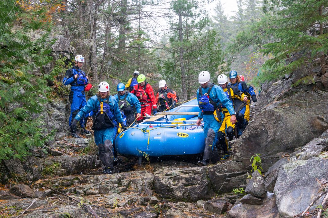 students from Algonquin College in Pembroke, portaging a raft.